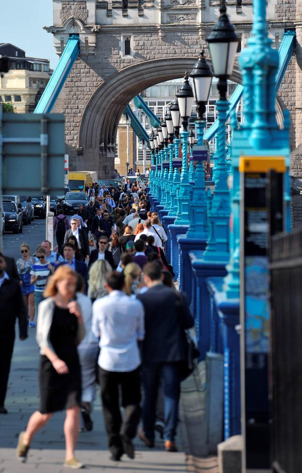Commuters walk across Tower Bridge, London, as commuters face travel misery trying to get to work because of a strike which has brought London Underground to a standstill.
