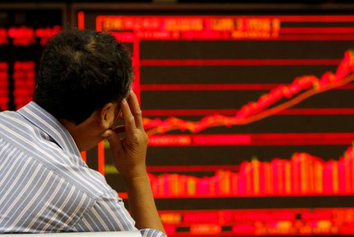 An investor watches an electronic board showing stock information at a brokerage office in Beijing. Photo: Reuters