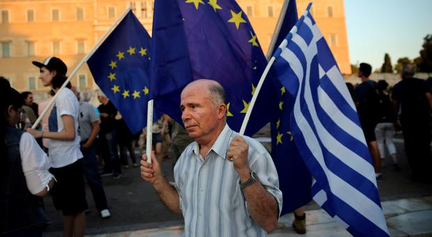 A pro-Euro protester holds a European Union and a Greek national flag during a rally in front of the parliament building in Athens. REUTERS/Alkis Konstantinidis