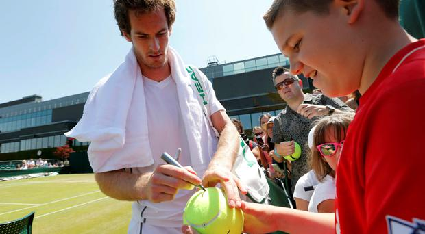 Andy Murray signs an autograph for a fan at Wimbledon yesterday ahead of today's semi-final with Roger Federer