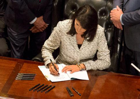 South Carolina Governor Nikki Haley signs legislation permanently removing the Confederate battle flag from the state capitol grounds. Photo: Reuters