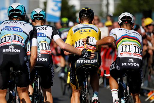 Yellow jersey Tony Martin is pushed to the line by team-mates yesterday, having broken his collarbone in a last kilometre crash