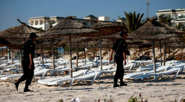 Police officers patrol the beach near the RIU Imperial Marhaba hotel in Sousse, Tunisia