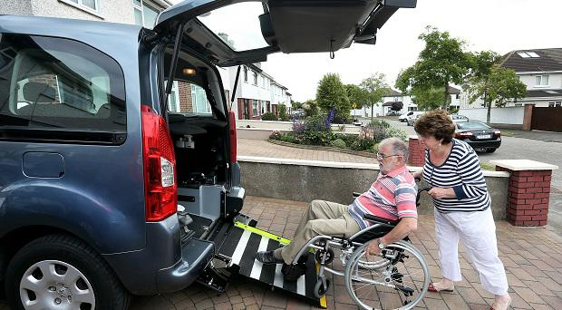 Marie helps Dave into their specially adapted car.