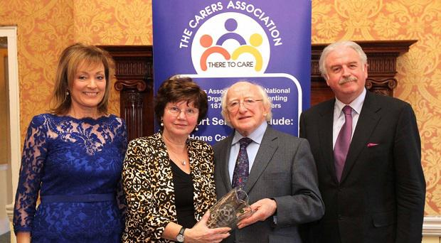 Marie collects her long-time carer award from President Higgins, watched by Mary Kennedy and Marty Whelan.