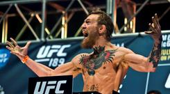 Featherweight Conor McGregor lets out a yell to his fans during the weigh in for UFC 189