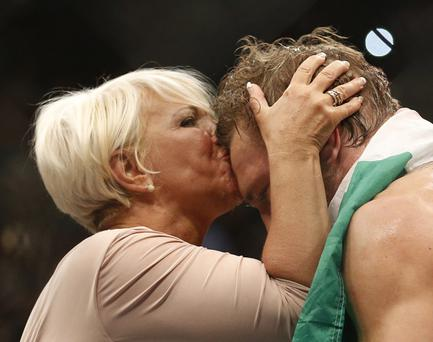 Conor McGregor gets a kiss for his mom Margaret after defeating Chad Mendes during their interim featherweight title mixed martial arts bout at UFC 189 Saturday, July 11, 2015, in Las Vegas. (AP Photo/John Locher)