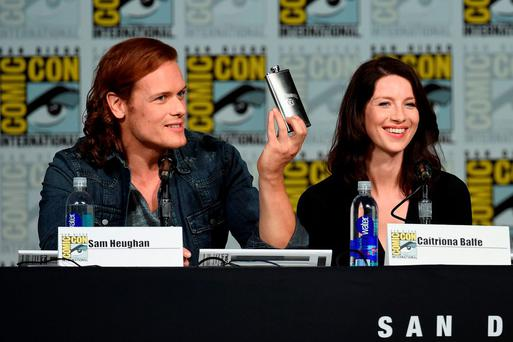 Actor Sam Heughan (L) and actress Caitriona Balfe speak onstage at the Starz: