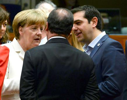 Greek Prime Minister Alexis Tsipras speaks with German Chancellor Angela Merkel (L) and French President Francois Hollande