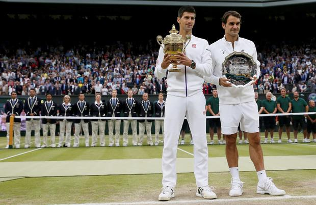Winner, Novak Djokovic of Serbia and runner up Roger Federer of Switzerland pose with their trophies after their Men's Singles Final match at the Wimbledon Tennis Championships in London, July 12, 2015. REUTERS/Stefan Wermuth