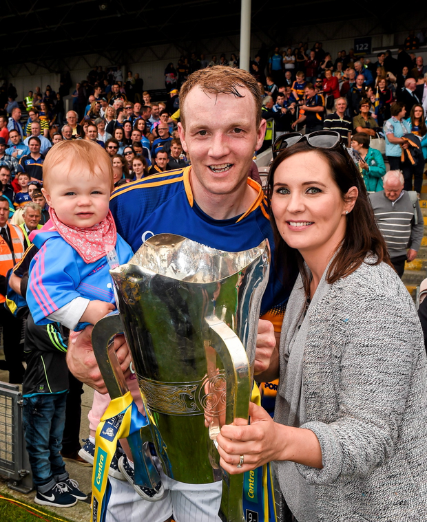 Tipperary's Lar Corbett holds the cup with his wife Elaine and one year old daughter Fay after the game