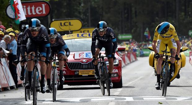 Nicolas Roche (centre) struggles up the final incline as the Sky riders, including yellow jersey Christopher Froome cross the line at the end of the 28km team time-trial yesterday GETTY