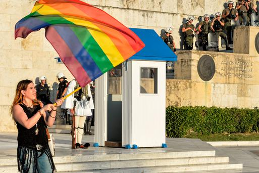 Greek riot police stand on the stairs leading to the Greek parliament as a leftist protester waves a rainbow calling for a 'NO' to any agreement with the creditors which would lead to further austerity measures for the nation (Getty Images)