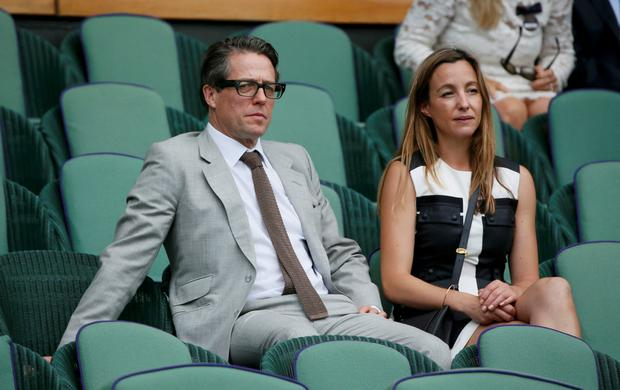 Actor Hugh Grant on Centre Court at the Wimbledon Tennis Championships in London with partner Anna Eberstein.