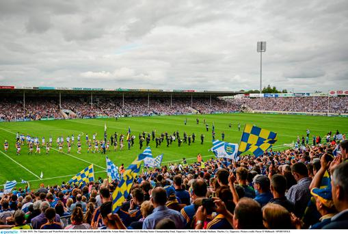 The Tipperary and Waterford teams march in the pre-match parade behind the Artane Band