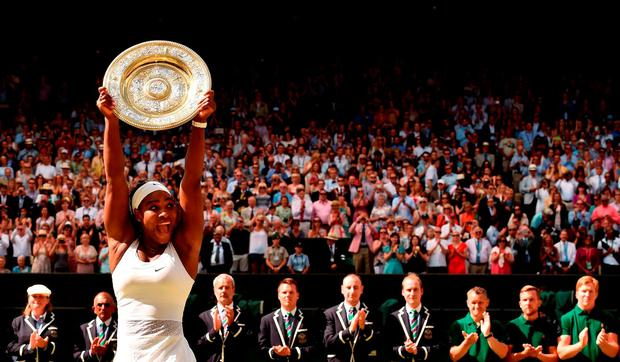 US player Serena Williams celebrates with the winner's trophy, the Venus Rosewater Dish, after her women's singles final victory over Spain's Garbine Muguruza on day twelve of the 2015 Wimbledon Championships