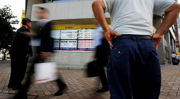 Passersby walk past an electronic stock quotation board outside a brokerage in Tokyo July 13, 2015. Japan's Nikkei share average rose on Monday as yet another strong rebound in Chinese shares soothed investor sentiment and as oil's fall boosted airliners and other energy users, though uncertainty on Greece's fate in the euro zone capped gains. REUTERS/Issei Kato