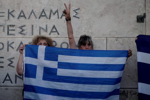 Anti-austerity protesters hold a Greek flag during a rally against the government's agreement with its creditors in front of the tomb of the unknown soldier in Athens (AP Photo/Petros Giannakouris)