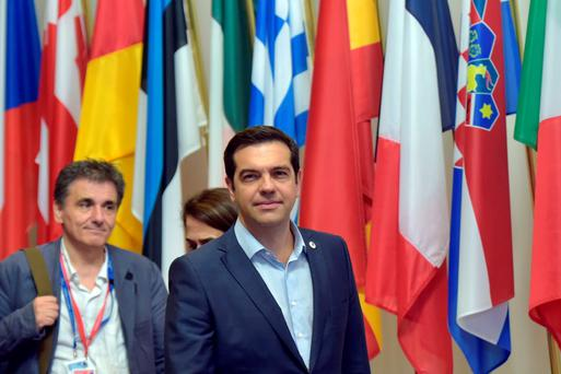 Greece's Prime Minister Alexis Tsipras (C) and Greek Finance Minister Euclid Tsakalotos (L) leave a euro zone leaders summit in Brussels. Photo: Reuters