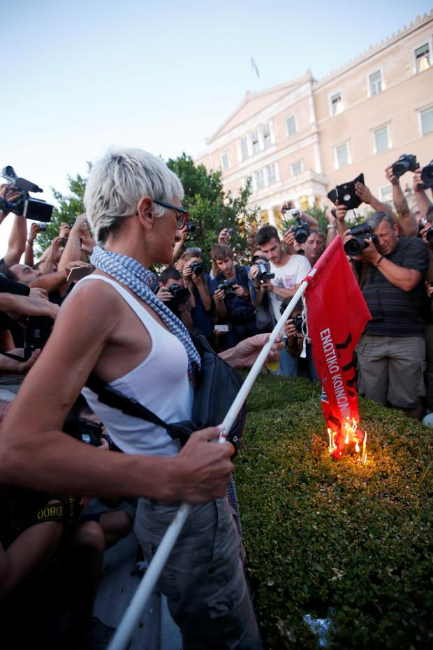 An anti-EU protester burns a leftist Syriza ruling party flag during a demonstration of about five hundred people in front of the parliament building in Athens, Greece July 13, 2015