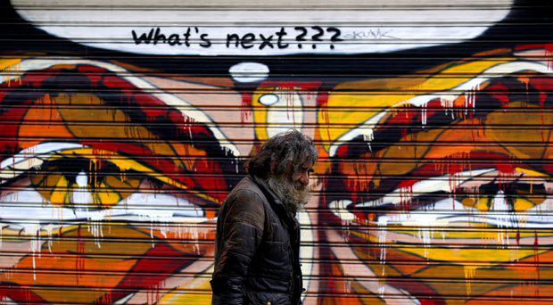 A man walks by a mural in Athens, Greece July 14, 2015, Prime Minister Alexis Tsipras faces a showdown with rebels in his own party furious at his capitulation to German demands for one of the most sweeping austerity packages ever demanded of a euro zone government. REUTERS/Yannis Behrakis