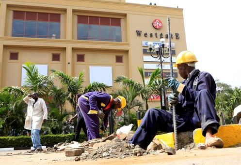 Construction workers dig holes to erect barriers at the reopened Westgate shopping mall, which was closed in the aftermath of an attack by militant gunmen in September 2013 that killed 67 people and injured many more, in capital Nairobi REUTERS/Noor Khamis