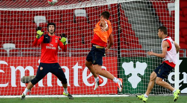 New signing Petr Cech (L) of Arsenal attempts to save the ball during the Arsenal FC open training session ahead of the match between Arsenal and Singapore during the 2015 Barclays Asia Trophy