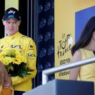 Britain's Christopher Froome waits for a signal of the master of ceremonies to leave the podium as the hostess walks off the podium of the tenth stage of the Tour de France cycling race over 167 kilometers (103.8 miles) with start in Tarbes and finish in La Pierre-Saint-Martin, France