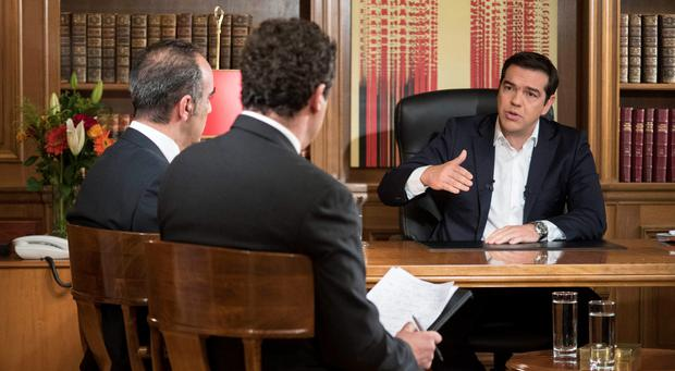 In this photo released by Greek Prime Minister's office on Tuesday, July 14, 2015, Greece's Prime Minister Alexis Tsirpas, right, speaks at journalists Panos Haritos and Antonis Alafogiorgos during an interview to ERT state TV from his office Photo: Andrea Bonetti/Greek Prime Minister's Office via AP
