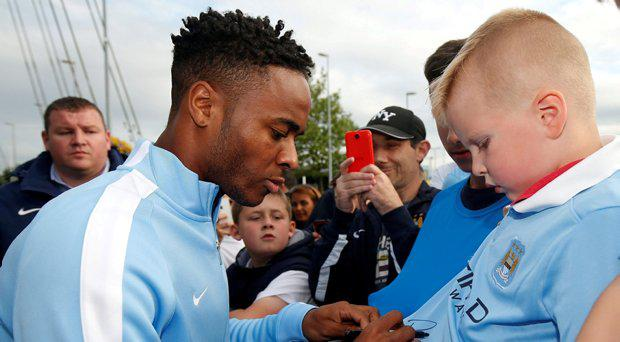 New Manchester City signing Raheem Sterling signs autographs for supporters as he leaves the club's Etihad Stadium in Manchester