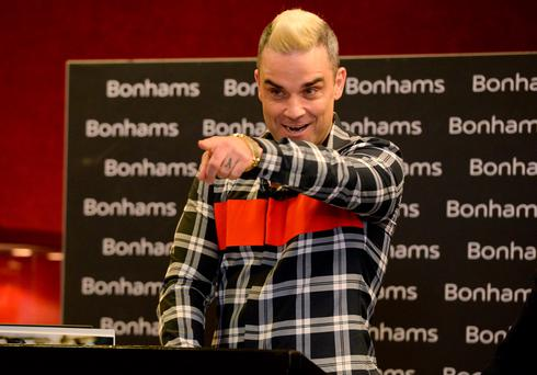 Robbie Williams auctions off items of his own memorabilia during a charity auction at Bonham's, London Credit: Anthony Devlin/PA Wire