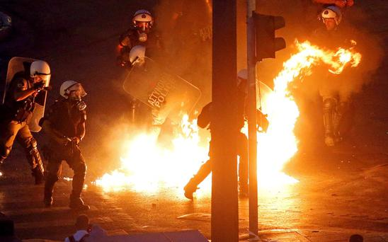 Riot police stand amongst the flames from exploded petrol bombs thrown by a small group of anti-establishment demonstrators in front of parliament in Athens, Greece REUTERS/Jean-Paul Pelissier