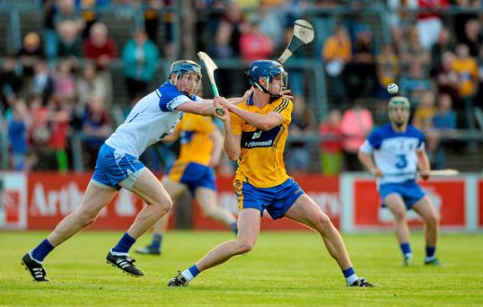 A determined Bobby Duggan, Clare, manages a clean strike, despite Austin Gleeson's best efforts