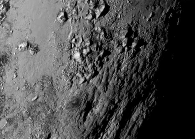 A new close-up image of a region near Plutos equator reveals a range of youthful mountains rising as high as 11,000 feet (3,500 meters) above the surface of the icy body. Photo: Reuters