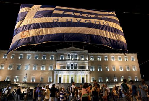Anti-austerity protesters lift a Greek flag in front of the Greek Parliament in Athens