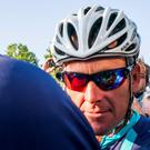Cyclist Lance Armstrong of the U.S. speaks to journalists as he leaves his bus before taking part in Geoff Thomas's 'One Day Ahead' charity event during a stage of the 102nd Tour de France cycling race from Muret to Rodez, France