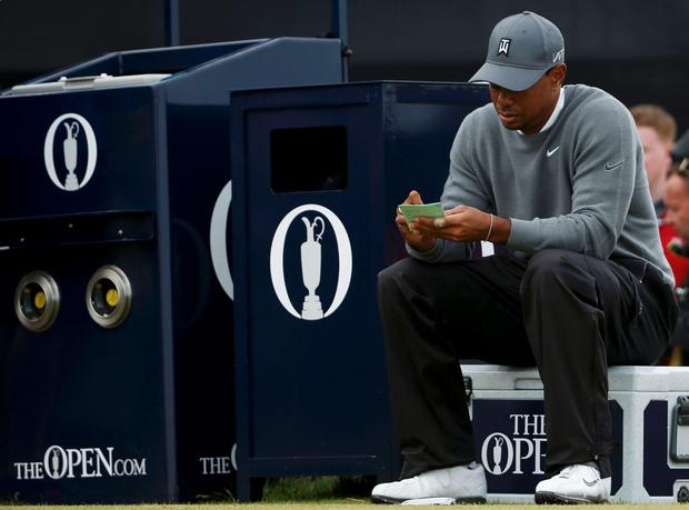 Tiger Woods of the U.S. marks his card as he sits on the 17th tee during the first round of the British Open golf championship on the Old Course in St. Andrews, Scotland, July 16, 2015. REUTERS/Lee Smith