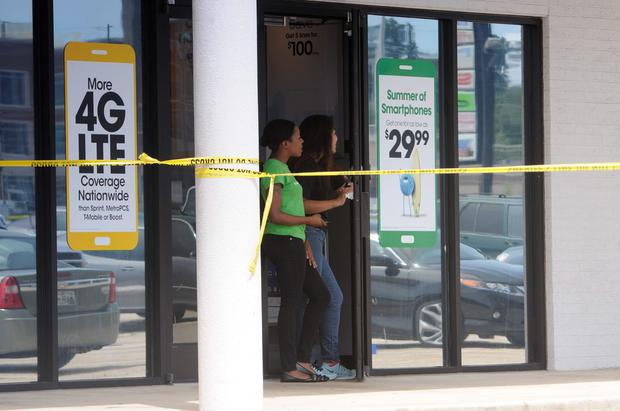 Store employees look out their door next to the Reserve Recruitment Center as the area is cordoned off after a shooting on Thursday (Tim Barber/Chattanooga Times Free Press via AP)