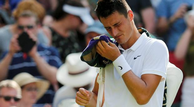 Bernard Tomic of Australia leaves the court after losing his match against Novak Djokovic of Serbia at Wimbledon earlier this month