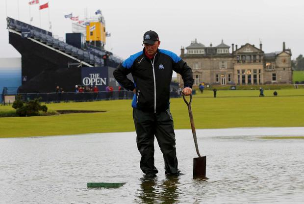 A member of the groundstaff stands in a puddle on the first fairway after torrential rain caused play to be suspended during the second round of the British Open golf championship on the Old Course in St. Andrews, Scotland, July 17, 2015. REUTERS/Paul Childs