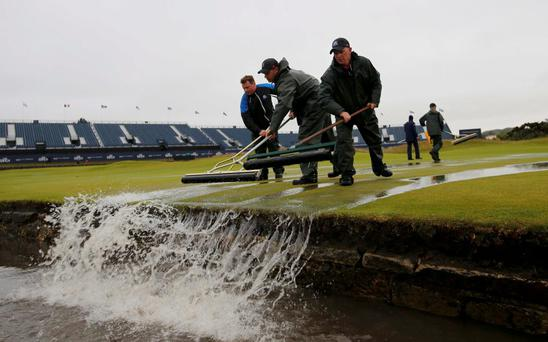 Groundstaff remove water from the first green after torrential rain forced play to be suspended during the second round of the British Open golf championship on the Old Course in St. Andrews, Scotland, July 17, 2015. REUTERS/Paul Childs