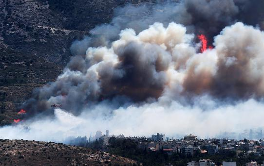 A firefighting helicopter drops water on a raging wildfire at the Kareas suburb, east of Athens, Greece July 17, 2015. Dozens of Athens residents fled their homes on Friday as wildfires fanned by strong winds and high temperatures burned through woodland around the Greek capital, sending clouds of smoke billowing over the city. REUTERS/Alkis Konstantinidis TPX IMAGES OF THE DAY