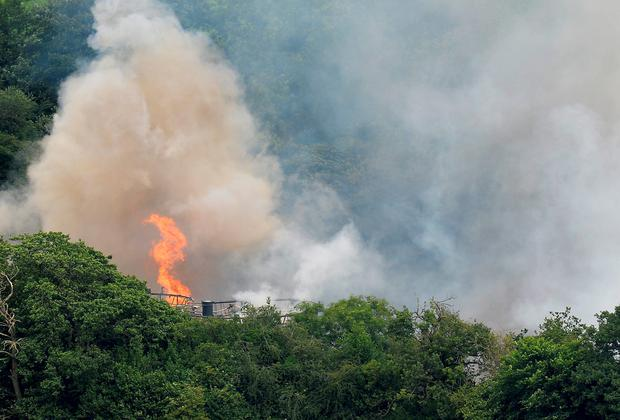 Flames are seen from Wood Flour Mills in Bosley, near Macclesfield, after an explosion and fire may have left four people trapped Credit: Martin Rickett/PA Wire