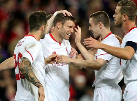 James Milner is congratulated by his team-mates after scoring for Liverpool