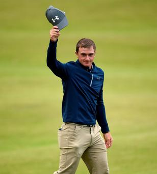 Ireland's amateur Paul Dunne tips his hat to the crowd on the 18th green of St Andrews