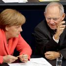 German Chancellor Angela Merkel and Finance Minister Wolfgang Schaeuble talk during a meeting of the Bundestag yesterday