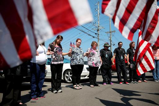 Miller-Motte Technical College students and others join in prayer across the highway from the strip mall where a gunman attacked the Armed Forces Career Center/National Guard Recruitment Office on July 17