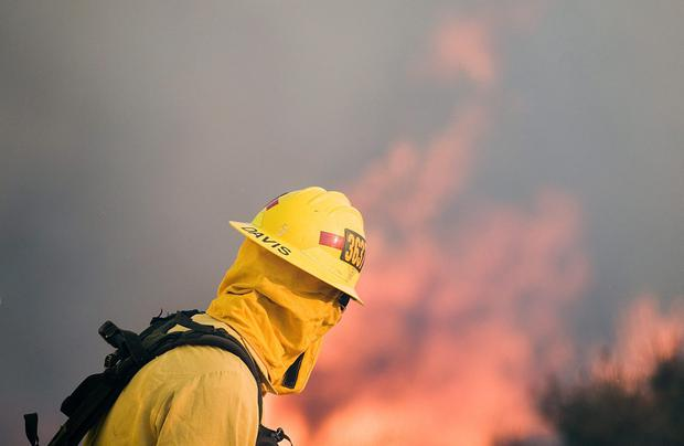 A firefighter watches flames in Southern California Credit: James Quigg/The Victor Valley Daily Press