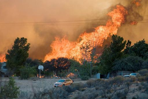 Flames rise from a fire over a cluster of homes in California Credit: James Quigg/The Victor Valley Daily Press