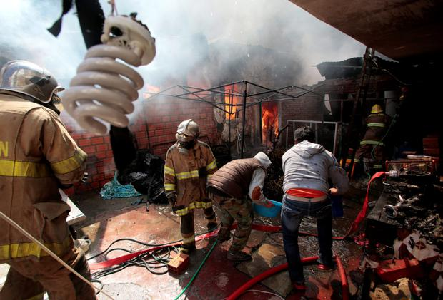 Fire fighters and locals try to control a fire in a popular district of La Paz Credit: REUTERS/David Mercado